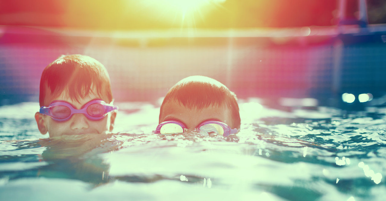 Two little kids in goggles swimming in pool at sunset