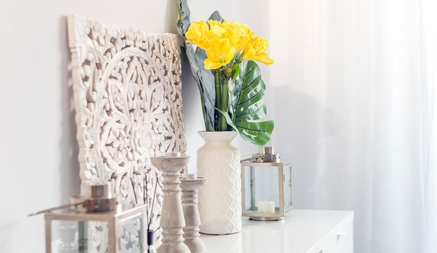 Yellow flowers in ceramic vase with wooden candlesticks and lantern decorating a shelf
